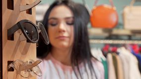 Woman shopping for sunglasses at the store. Selective focus on a pair of sunglasses, woman trying on eyewear on the background. Fashion, eyesight, uv stock video footage