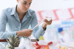 Woman checking a long receipt royalty free stock image