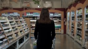 Woman shopping at the supermarket, follow shot from back of young woman with trolley in shopping center, alcohol store. stock video footage