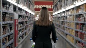Woman shopping at the supermarket, follow shot from back of young woman with trolley in shopping center, alcohol store. Woman shopping at the supermarket stock video