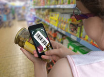 Woman is shopping in supermarket and scanning barcode with smartphone in grocery store. Royalty Free Stock Image