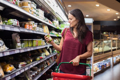 Woman shopping in supermarket. Young woman shopping in grocery store. Mature woman checking food label in supermarket. Latin woman holding shopping basket and stock images