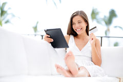 Woman shopping on tablet computer and credit card. Sitting in sofa smiling happy. Pretty cheerful asian caucasian woman shopper buying spending money online on Stock Photography