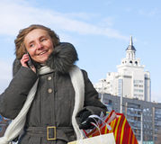 Woman with shopping and a telephone in the city. Cheerful Woman with shopping on the phone Stock Photo