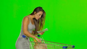 Woman shopping with trolley at supermarket and checking a paper list. Green screen. Young woman shopping with trolley at supermarket and checking a paper list stock video
