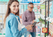 Woman shopping and using her phone Royalty Free Stock Image