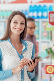 Woman shopping and using her phone Royalty Free Stock Photo