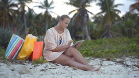 Woman after shopping using tablet PC on the beach. Young woman sitting on the beach and using touch pad, shopping bags nearby. Vacation with pad stock video