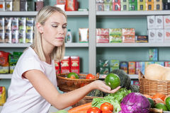 Woman shopping vegetables. Pretty woman buying some vegetables Stock Image