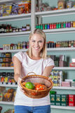 Woman shopping vegetables. Pretty woman showing some vegetables Royalty Free Stock Images