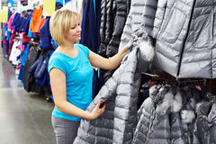 Woman shopping for winter jacket in shop Royalty Free Stock Photos