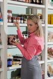 Woman shopping. Young woman choosing fruit jams Royalty Free Stock Photo