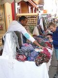A woman shops for a  colorful scarf Stock Photos