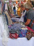 A woman shops for a  colorful scarf Royalty Free Stock Photo