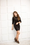 Woman in short black dress leaning against white bricked wall Royalty Free Stock Images