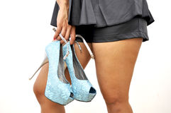 Woman short black shorts holds pair of high heels Royalty Free Stock Photos