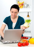 Woman with short dark hair looking for cooking recipe in the int Royalty Free Stock Images