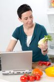 Woman with short dark hair looking for cooking recipe in the int Stock Photography