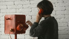 Woman with short hair dials in retro phone. A woman with short hair dials in retro red phone stock video footage