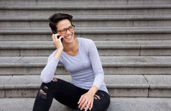 Woman with short hair and glasses talking on mobile phone Royalty Free Stock Image