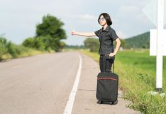 Woman short hair with luggage hitchhiking and thumbs up Stock Images