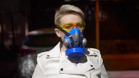 A woman with short hair a respirator outdoors. closeup