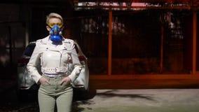 A woman with short hair a respirator outdoors. medium shot