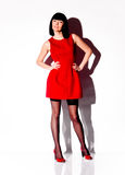 Woman in short red dress posing in studio against white background Stock Photo