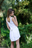 Woman in short white dress, lush vegetation as background. Back view of a slim and good looking woman in short white dress with shapely long legs looking down royalty free stock images
