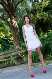 Woman in short white dress, lush vegetation as background. Slim and good looking woman in short white dress with shapely long legs and bolt red high heels, lush Stock Photos