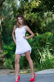 Woman in short white dress, lush vegetation as background. Slim and good looking woman in short white dress with shapely long legs and bolt red high heels, lush Stock Photo