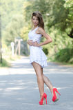 Woman in short white dress and red high heels. Back view woman in short white dress with slim shapely long legs and red high heels, looking over shoulder to the Royalty Free Stock Photo