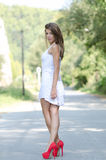 Woman in short white dress and red high heels Royalty Free Stock Image
