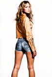 Woman in shorts. Young woman in jeans shorts and leather jacket, stdio shot, white background Stock Images