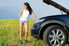 Woman in shorts with broken down car Stock Images