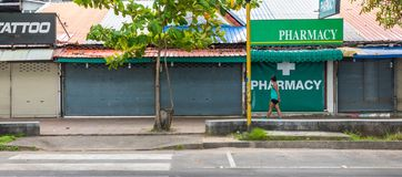 Woman in Green walking past Pharmacy royalty free stock photography