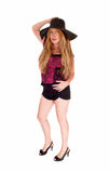 Woman in shorts and hat standing. Royalty Free Stock Photography