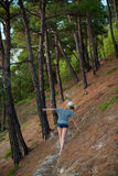Woman in shorts and hat walking the summer forest Royalty Free Stock Image
