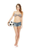 Woman in shorts holding foot ball. Stock Images