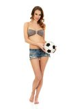 Woman in shorts holding foot ball. Royalty Free Stock Image