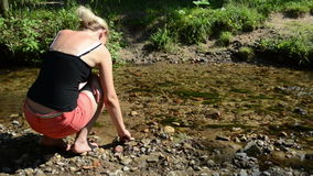 Woman shorts sit stream throw pebble stones flowing water. Woman with shorts sit near stream and throw pebble stones into flowing water stock video