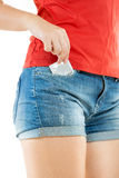 Woman in shorts taking out packed condom Stock Images