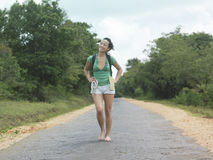 Woman In Shorts Walking Barefeet On Rural Road. Full length portrait of a young woman in shorts walking barefeet on rural road Stock Image