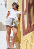 Woman in shorts at the wall Royalty Free Stock Image