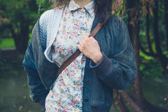 Woman with shoulder bag in wooded park. Royalty Free Stock Photography