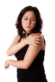 Woman with shoulder pain. Beautiful woman holding her shoulder with pain and ache,wearing a sporty black tank top, isolated stock photography