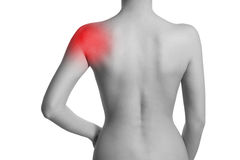 Woman with shoulder pain. Shoulder is highlighted by red colour stock images
