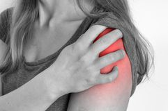 Woman with shoulder pain is holding her aching arm. Black and white photo stock images