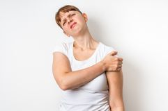 Woman with shoulder pain is holding her aching arm. Isolated on white background stock photos