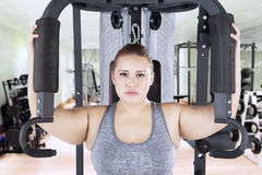 Woman with shoulder press machine in fitness center. Portrait of overweight woman looking at the camera while exercising on a shoulder press machine in the stock photography